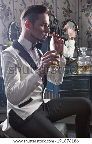Elegant gentleman with cigar and whisky in the club - stock photo