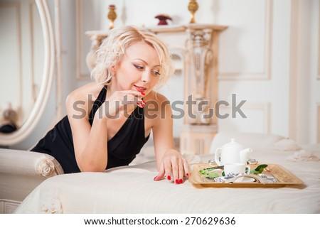 Elegant girl in evening dress posing in an elegant bedroom - stock photo