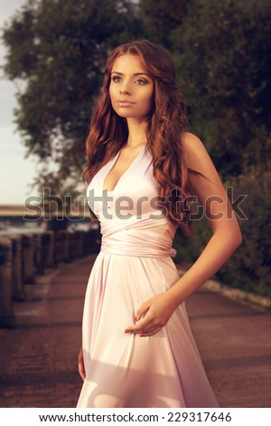 Elegant girl in evening dress posing outdoors at sunset. Fashion style portrait of young pretty caucasian brunette woman in soft lovely sun backlight. - stock photo