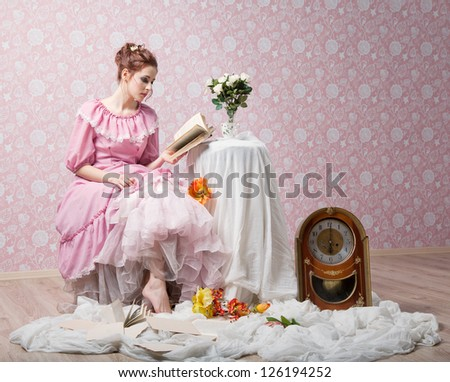 Elegant girl in pink clothes is reading near table with flowers - stock photo