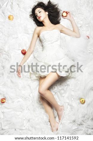 Elegant girl sleeping on white fabric next to apple - stock photo