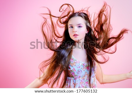 Elegant girl with natural make-up and beautiful long hair in motion posing over pink background. Fashion. Hairs. - stock photo