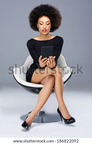 Elegant glamorous African American woman sitting in a black cocktail dress and high heels in a modern design armchair reading her tablet computer - stock photo