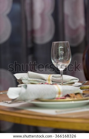 elegant glass and tidy napkin on table in luxury dining room