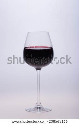Elegant glass filled with red wine standing on the white background - stock photo