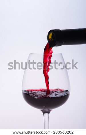 Elegant glass is filled with the red wine isolated on the white background - stock photo