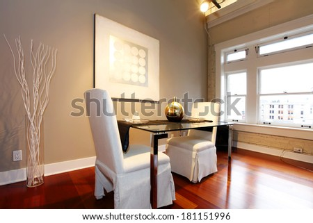 Elegant glass table with white luxury chairs in modern reconstructed living room. Decorated with glass vase and white dry branches and wall picture