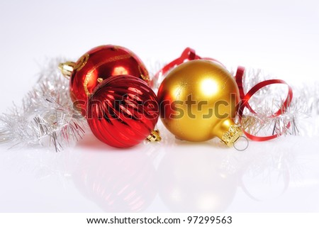 Elegant glowing red and golden-colored Christmas balls on a slightly textured reflective surface.