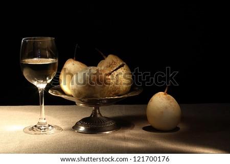 Elegant goblet of white dry wine near brass fruit bowl with pears - stock photo