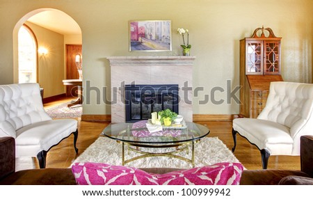 Elegant gold and pink fireplace in living room interior with white chairs. - stock photo