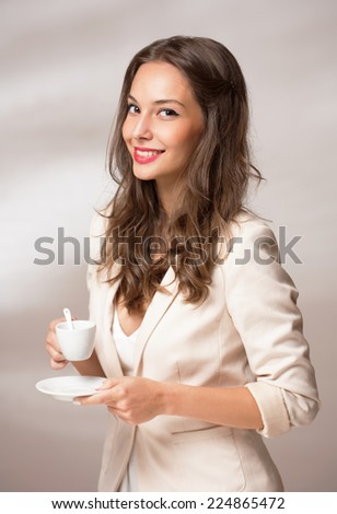Elegant gorgeous young brunette woman with a cup of gourmet coffee. - stock photo