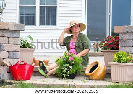 Elegant Grandma posing as she pots up plants on the steps of her home in terracotta pots to decorate the patio and house - stock photo