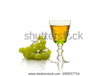 Elegant green tinted cut glass goblet of white wine or grape juice with a bunch of fresh green grapes alongside on a white reflective background with copyspace - stock photo