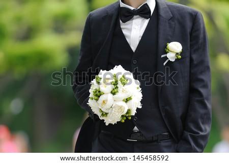 elegant groom holding flowers in park - stock photo