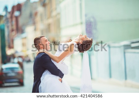 elegant groom lifting up his beautiful brunette bride on the background of old white wall - stock photo