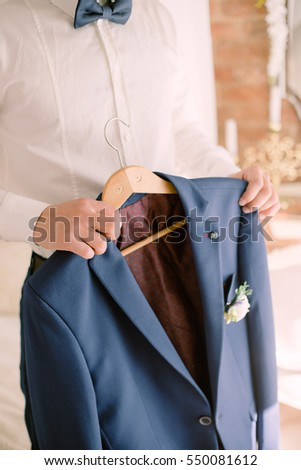 Elegant groom wearing white shirt and blue bow tie flower beautiful boutonniere holding jacket with on the hanger.