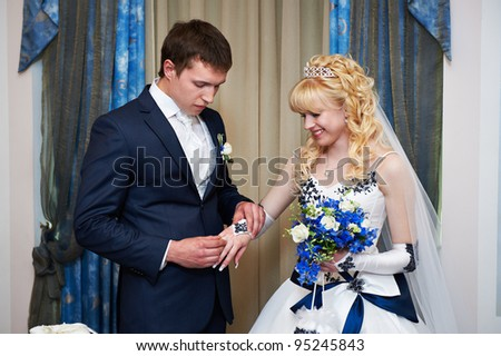 Elegant groom wears wedding ring happy bride. Solemn registration of marriage. - stock photo