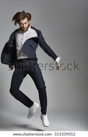 Elegant guy with beard jumping