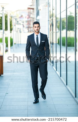 elegant handsome business man walking on the street - stock photo