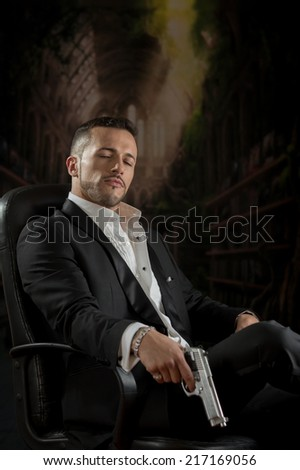 Elegant handsome latin man spy hitman assassin looking down sitting in a chair holding a gun over dark background - stock photo