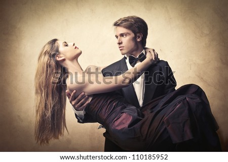 Elegant handsome man holding his beautiful girlfriend in his arms - stock photo