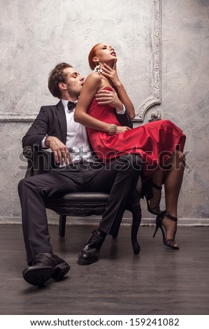 Elegant handsome man kissing his girlfriend in a shoulder. Girl sitting on his knees  - stock photo