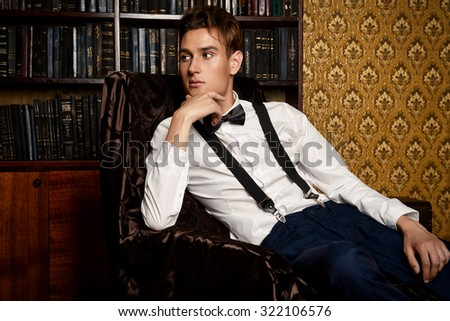 Elegant handsome young man sitting by the fireplace in a room with classic vintage interior. Fashion shot. - stock photo