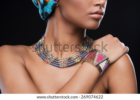 Elegant jewelry. Cropped picture of beautiful African woman wearing a headscarf and jewelry while standing against black background - stock photo
