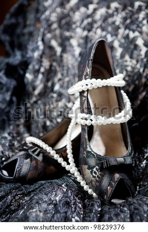 Elegant lace high heels shoes ona a black lace material. - stock photo