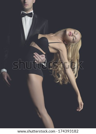 Elegant lady blonde at the hands of a young man in suit - stock photo