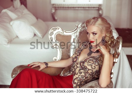 Elegant lady. Fashion beautiful sensual blond woman with makeup in luxurious prom dress with bijou, posing on modern armchair with sliver frames. - stock photo