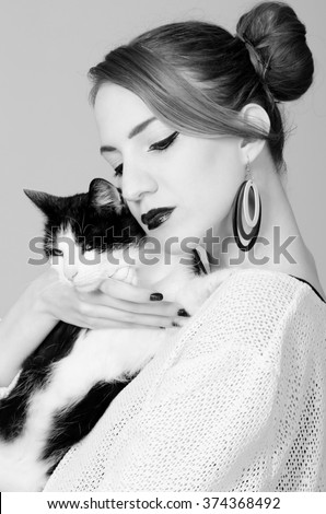 Elegant lady holding black and white cat isolated on gray background..