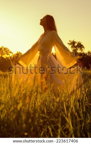 Elegant lady standing on the meadow on sunny autumn day. - stock photo