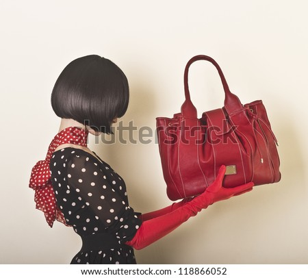 Elegant lady with stylish short hairstyle holding a bag - stock photo