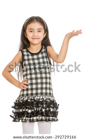 Elegant little dark-haired girl with long hair and plaid trendy short dress features a hand toward a larger plan - isolated on white background - stock photo