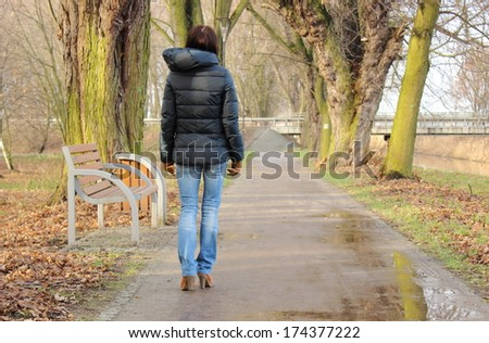 Elegant lonely woman walking in autumn park on cold rainy day, sad woman in park - stock photo