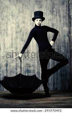 Elegant male mime artist in top hat posing with umbrella by a grunge wall. - stock photo