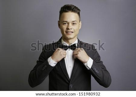 Elegant man fixing bow-tie, smiling, stylish, half body, gray background, studio shoot. - stock photo