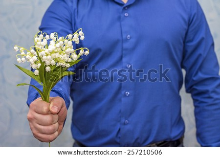 Elegant man holding lilies of valley. Gift on March 8 - stock photo