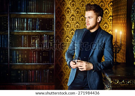 Elegant man in a suit with glass of beverage stands in vintage room. Fashion. - stock photo