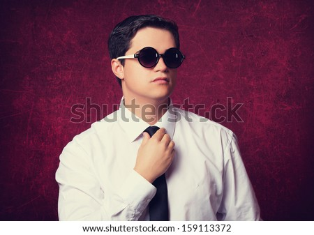 Elegant man in sunglasses at red background. - stock photo