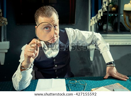 Elegant man looking through a magnifying glass