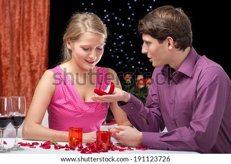 Elegant man proposing to his girlfriend in exclusive restaurant  - stock photo