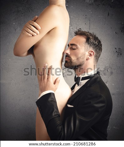 Elegant man smelling a beautiful sexy girl - stock photo