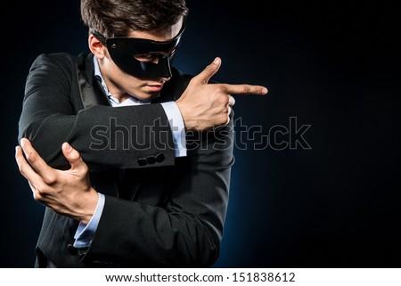 Elegant man wearing black mask posing indoors - stock photo