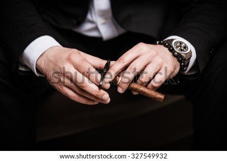 elegant man wearing black suit and white shirt cut Cuban cigar indoor shot, closeup - stock photo