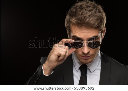 Elegant masculinity. Closeup studio portrait of a handsome fierce suited young businessman looking to the camera over his sunglasses on black background copyspace