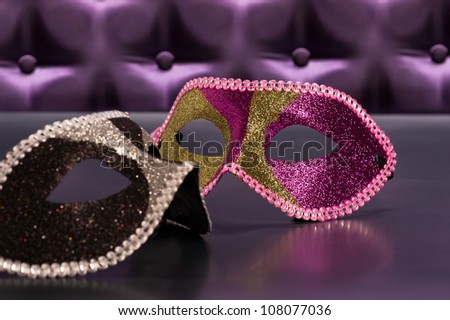 Elegant mask for Masquerade in front of a button tufted purple silk background - stock photo