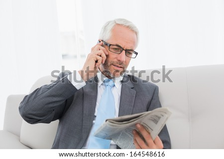 Elegant mature businessman using cellphone while reading newspaper on sofa in living room at home