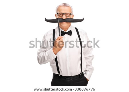 Elegant mature man with a black suspenders and bow-tie holding a fake mustache above his lips and looking at the camera isolated on white background - stock photo